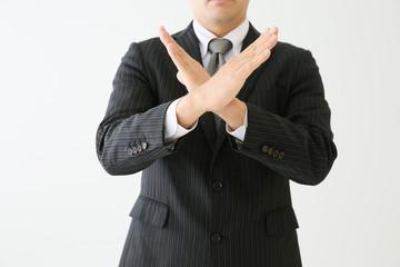 スーツを着た人が両手で×を作っている