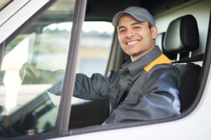 トラックの運転席に座る男性が笑顔でこちらを見ている